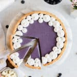 Blueberry white chocolate ganache tart with three pieces sliced. One is being removed.