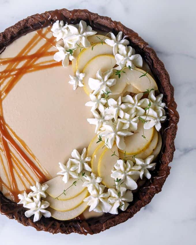Overhead shot of decorations with caramel, sliced pears, and whipped cream