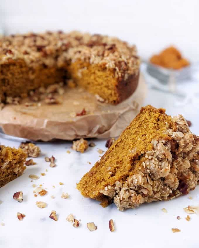 A round pumpkin coffee cake with two slices taken out, laying in front of the main cake.