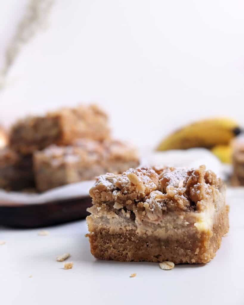 One square slice of the peanut butter banana oatmeal bar close up with a stack of bars behind it
