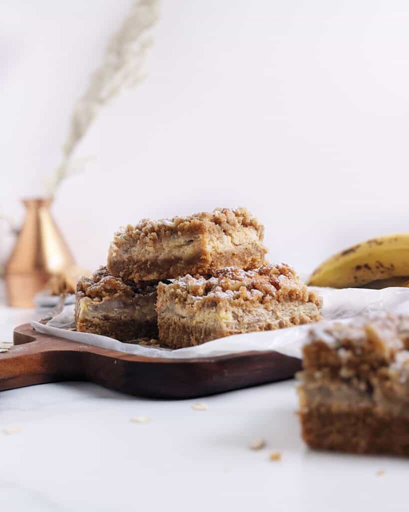 stack of peanut butter banana oatmeal bars with bananas in the background