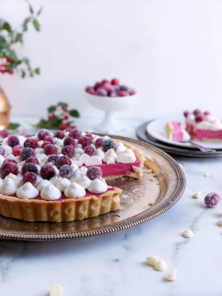 White chocolate cranberry tart with a slice removed and on a plate