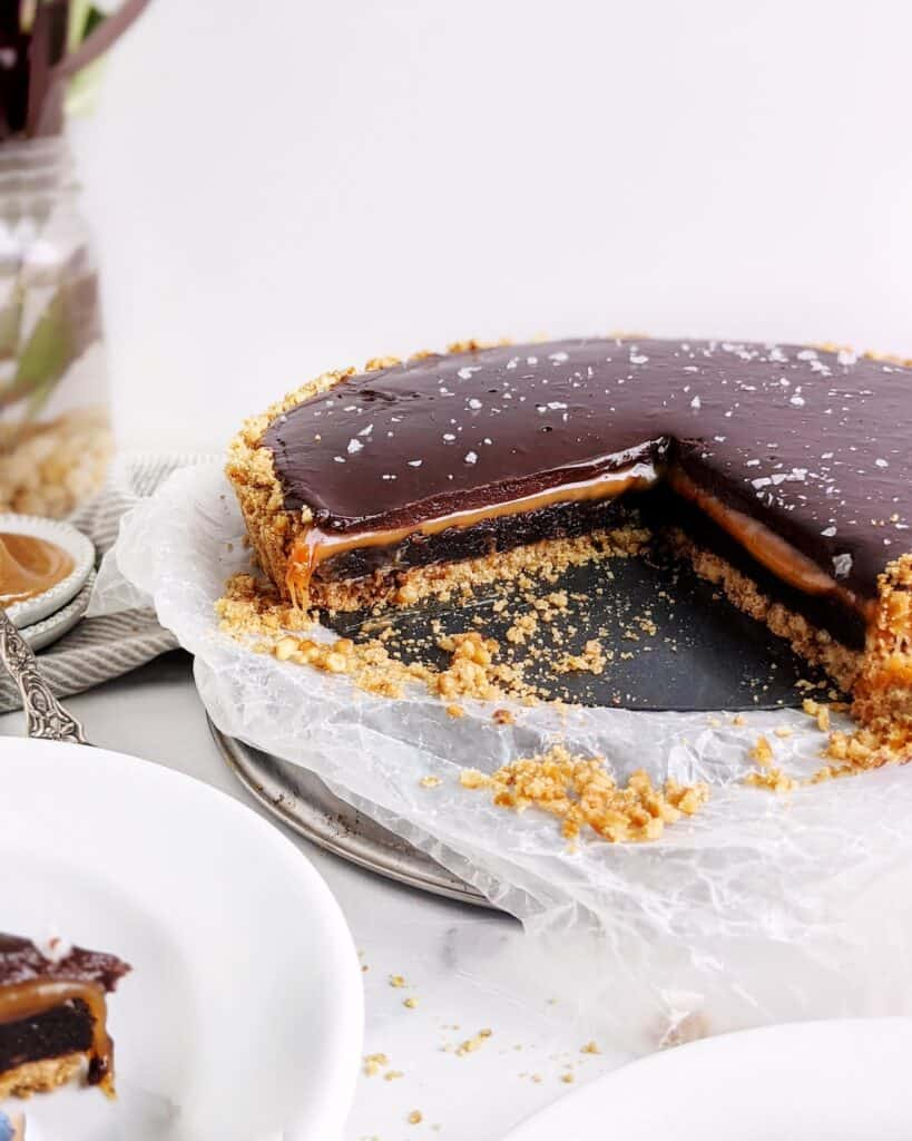 cross section of the caramel brownie pretzel pie with two slices removed. flaky salt is scattered on top of the ganache