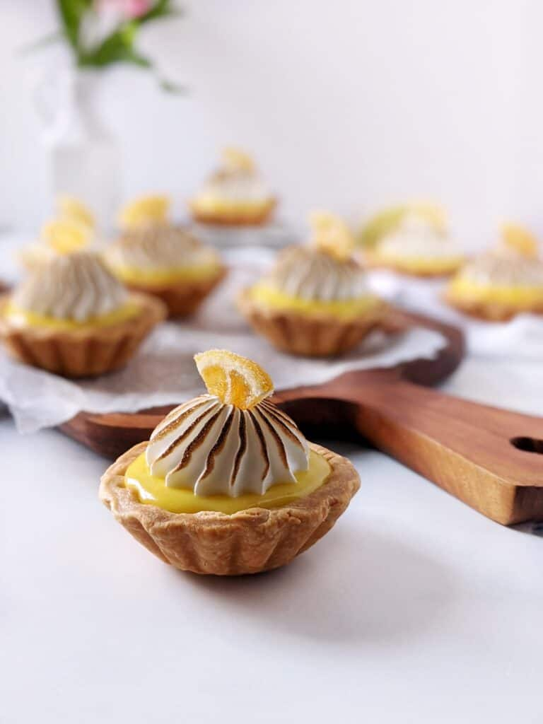 Straight on shot of one lemon meringue tartlet with multiple in the background.
