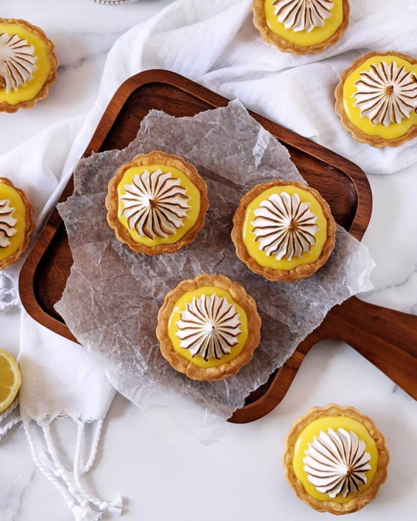 Overhead shot of multiple lemon meringue tartlets with torched tops.
