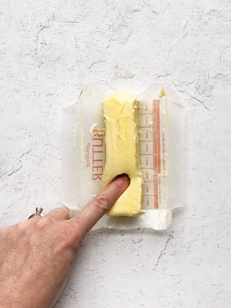 Finger pushing deep into a stick of butter that is too soft