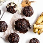 Overhead shot of numerous double chocolate banana muffins. The muffin in the center of the frame is unwrapped. Bananas and a glass of milk sit off on the side