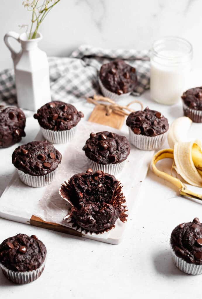 One double chocolate banana muffin is torn open to show the melted chocolate chips.