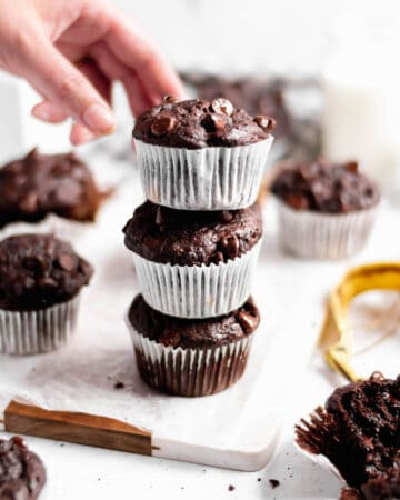 A stack of three double chocolate banana muffins. A had reaching in to take the top muffin.