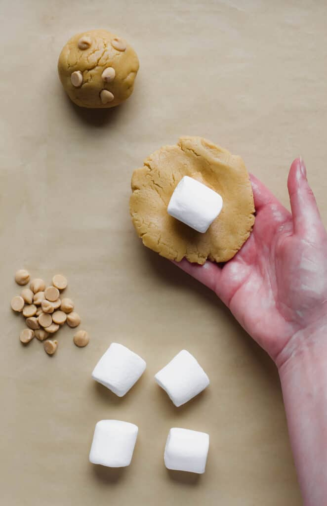 A hand holds a flattened piece of dough with a dollop of peanut butter and marshmallow in the center