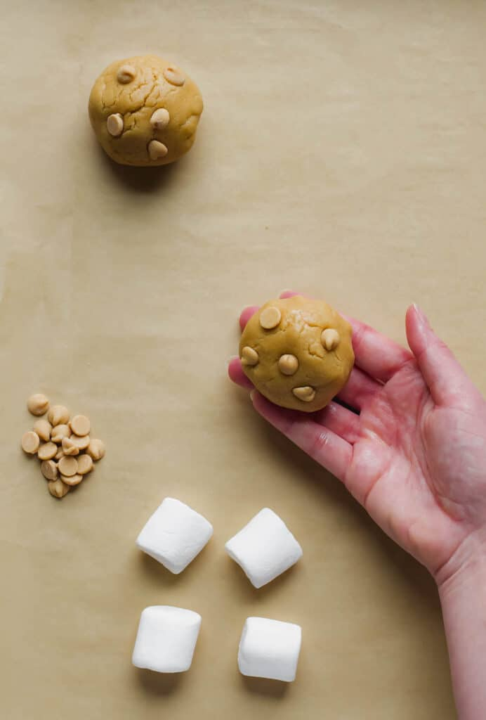 A hand holds one stuffed cookie dough ball, studded with peanut butter chips