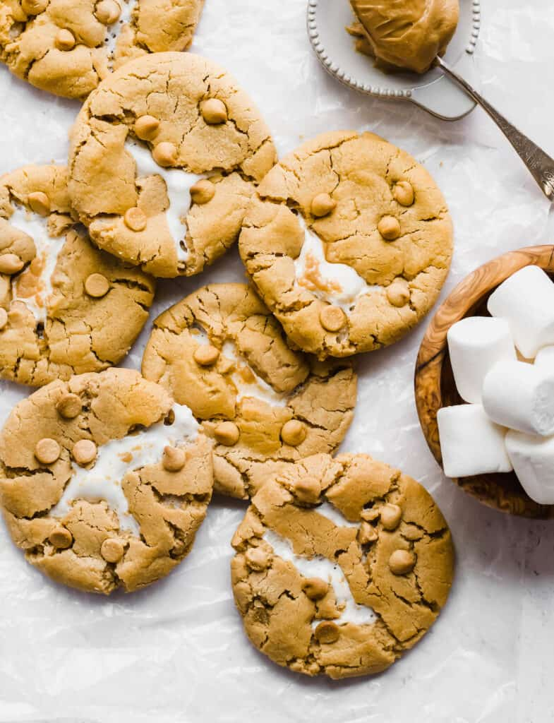 Overhead shot of an array of baked cookies. The marshmallow peaks out of the center of each cookie.