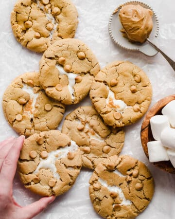 Overhead shot of an array of baked cookies. A hand reaches in to remove a cookie