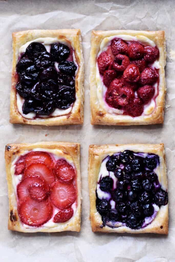 Overhead shot of four cheese danishes. Cherry, raspberry, strawberry, and blueberry.