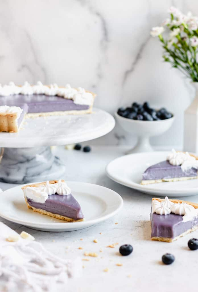 Blueberry white chocolate ganache tart with three slices removed. Two are on plates, one is on the table with a bite removed.