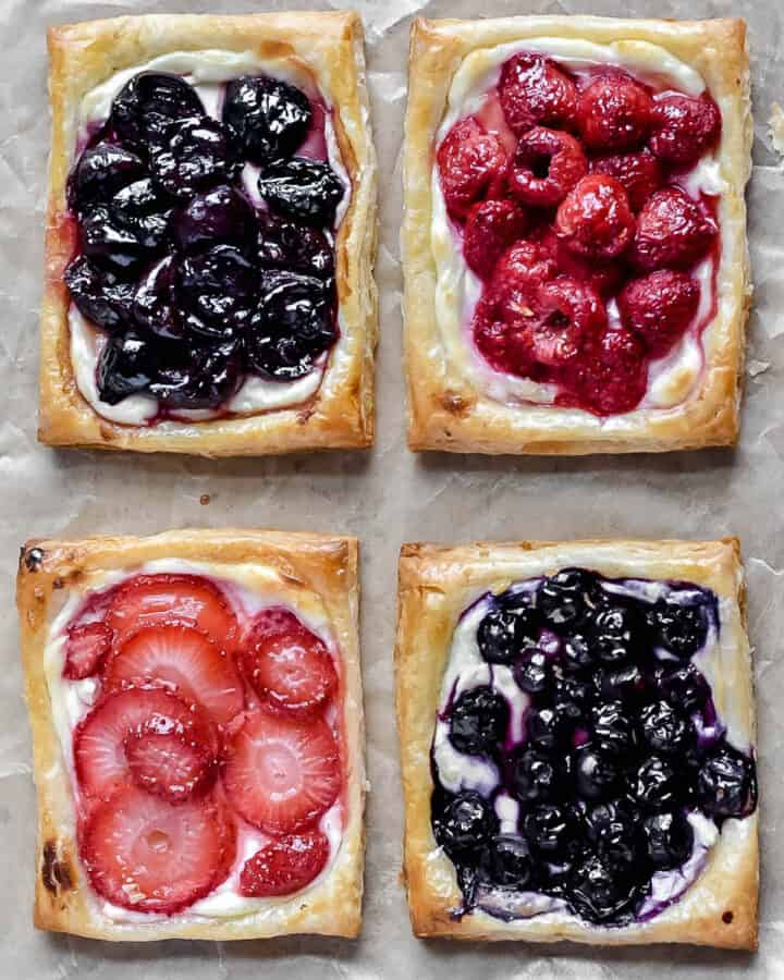 Overhead shot of four baked fruit & cream cheese puff pastry danish. Strawberry, blueberry, raspberry, and cherry