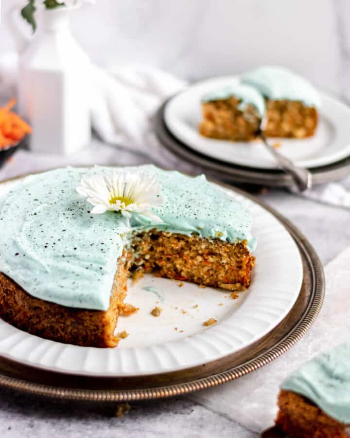 A carrot snack cake with cream cheese frosting sits on a. plate with two slices removed. One slice is on a smaller plate in the background