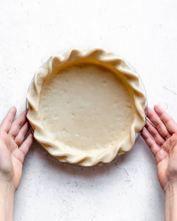A crimped raw pie dough with two hands about to lift it up