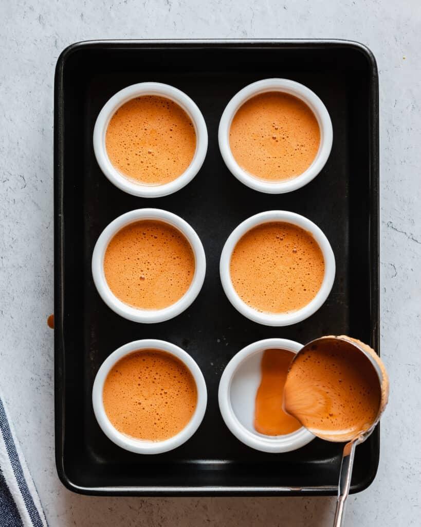 6 ramekins sit in a casserole dish. Thai Tea custard is being ladled into the ramekins.