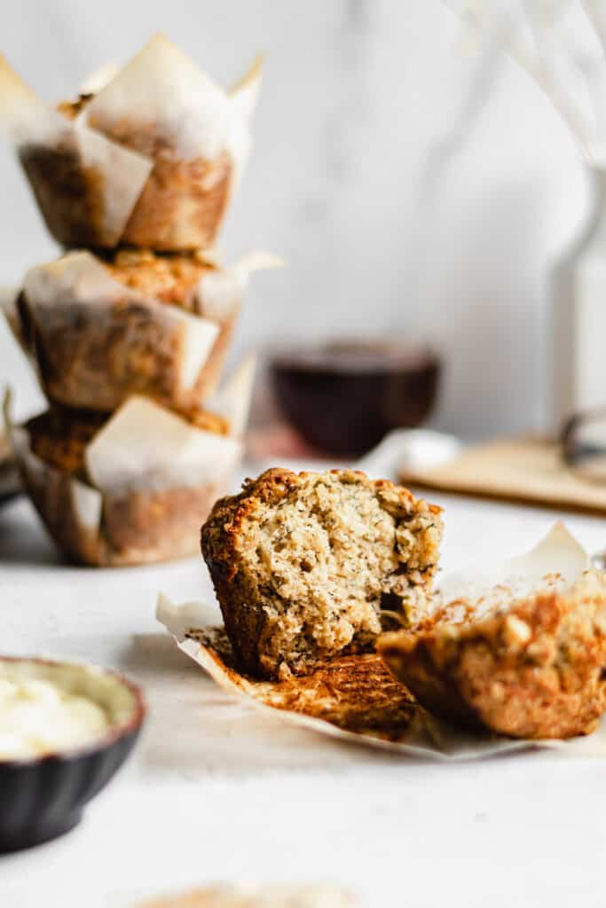 A banana nut muffin broken open to show the inside. A stack of muffins is stacked in the background.